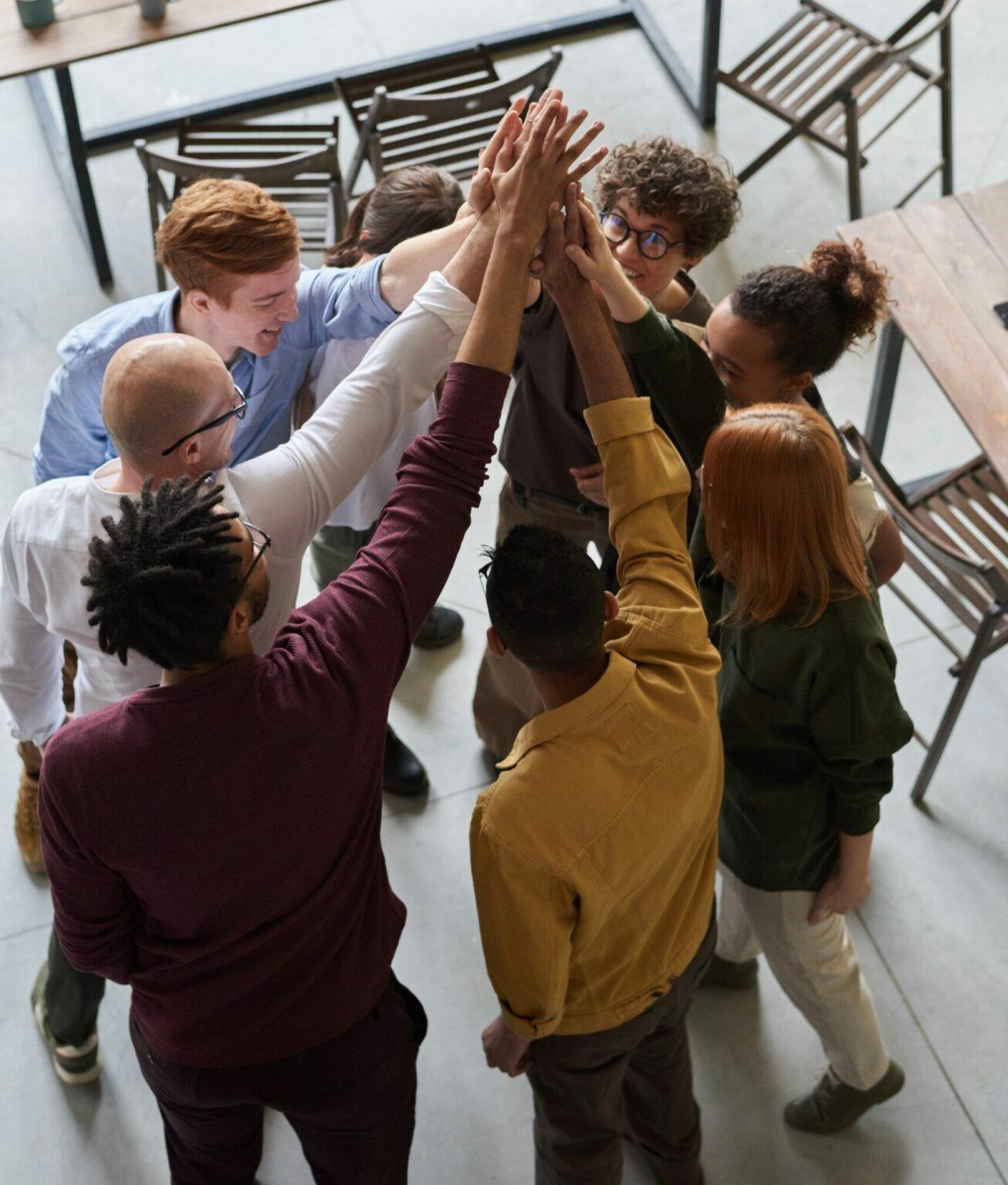 Gruppe von Menschen streckt die Hände in die Mitte