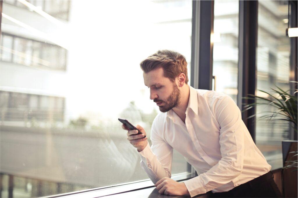 Mann steht am Fenster und benutzt Smartphone