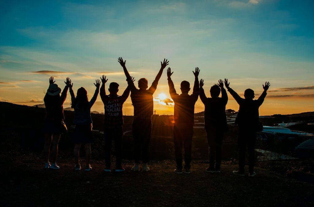 Gruppe von Menschen streckt die Hände in die Höhe vor der untergehenden Sonne